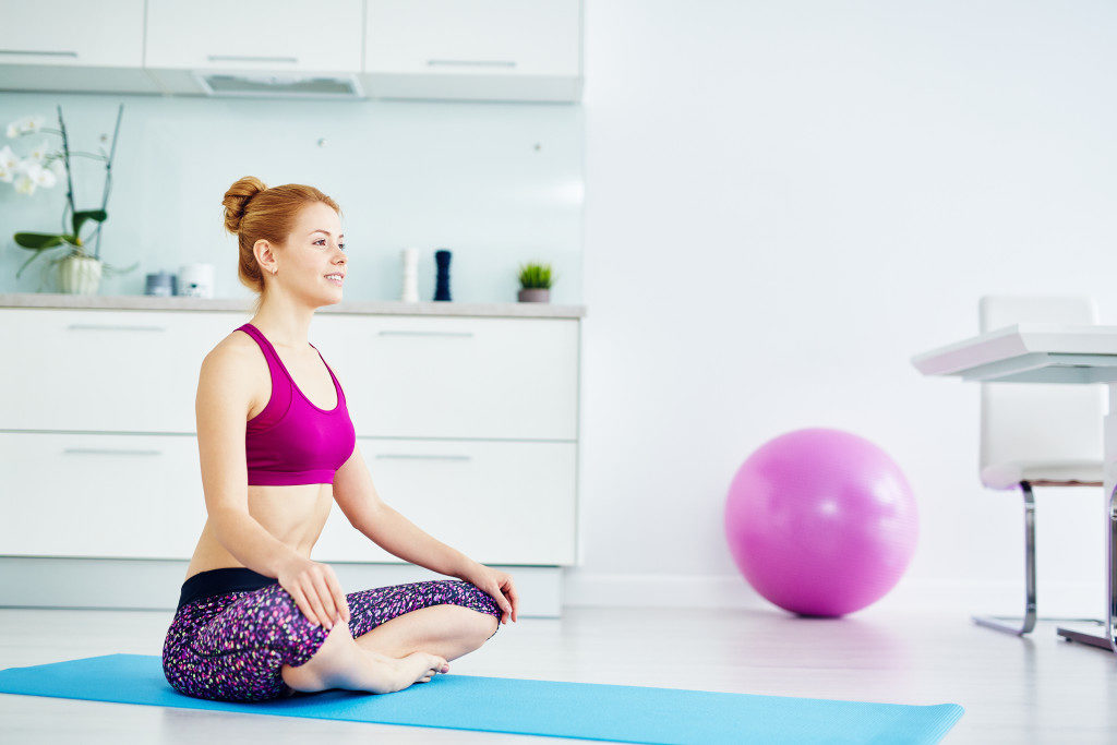 red haired woman doing yoga exercises at home