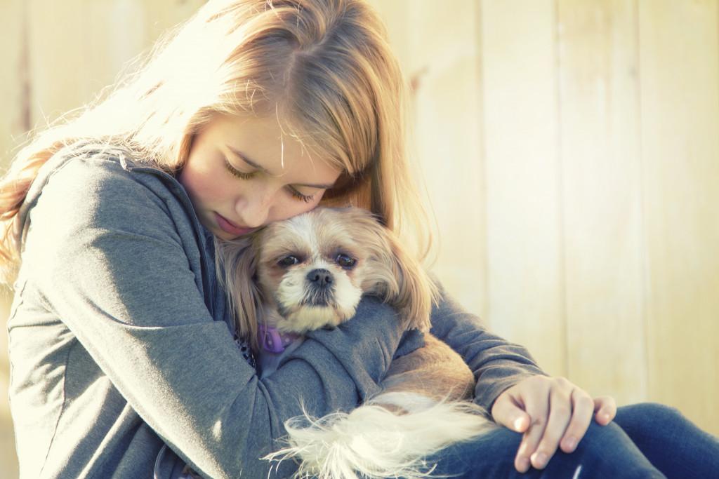 Sad female hugging dog